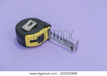 Tape measure in millimetres and inches isolated on black