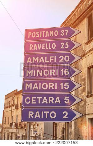 A road sign indicating the distance to the main resort towns of the Amalfi coast in the backlight of the sun. Cities: Positano, Ravello, Amalfi, Minori, Maiori, Cetara, Raito.