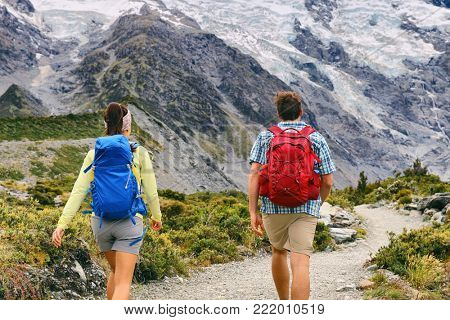 Hiking people walking on mountain trail trekking with backpacks. Hikers couple backpacking in nature, outdoor active lifestyle. Two young adults from behind.