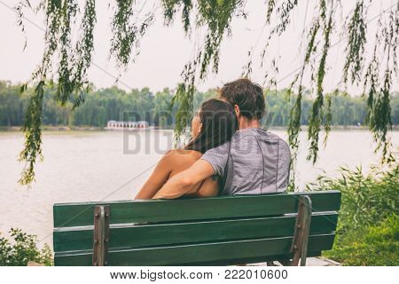 Couple sitting on park bench honeymoon China travel. Young tourists in love looking at lake. Beijing summer palace, famous tourist attraction. Happy vacation concept.