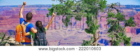 Grand Canyon hikers tourists couple success banner with arms up happy for hike achievement. Backpackers hiking with backpacks standing at view of famous american landmark, USA trip travel.