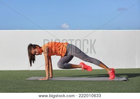 Fitness ab exercise for sexy toned stomach. Gym girl training abs working out core body with mountain climbers knee twist exercising obliques muscles . Asian woman on exercise mat outdoor at home.