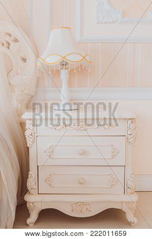 Bedside pedestal in bedroom. Pure beige colors