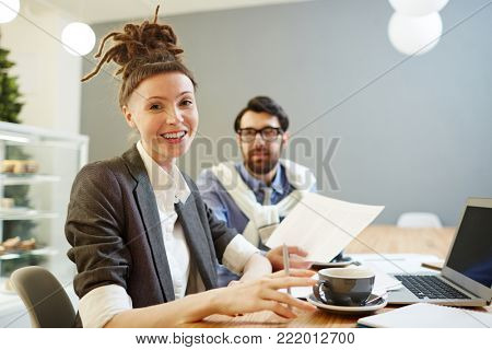 Successful young businesswoman with dreadlock bun on head looking at camera by her workplace