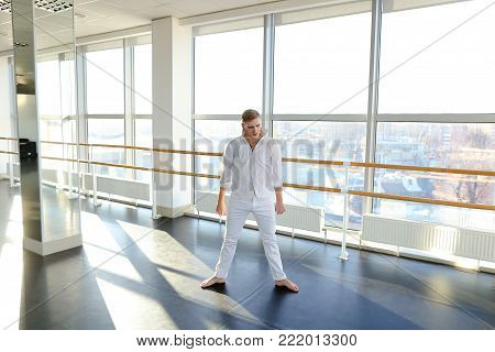 Young person jumping and dancing in street style way barefoot . Guy training at gym studio. Concept of learning hip hop and break dance technique.
