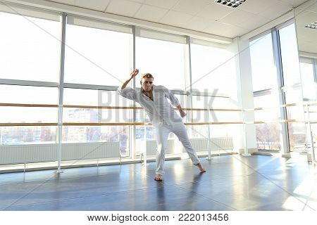 Dance winner doing warm up before training at studio with mirror. Young person wears white shirt and pants. Concept of advertisement of dance school.