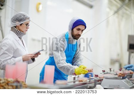 Control staff in uniform checking weight and quality of seafood during processing