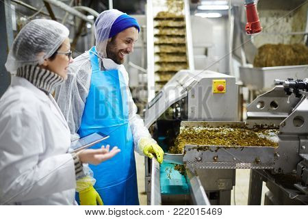 Two workers of seafood plant having talk by producing-line of seaweed salad