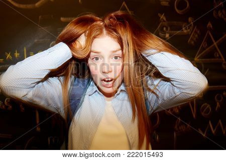 Ginger head girl ruffling her long hair with confused expression