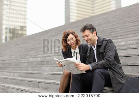 engineers male and female find article about company in newspaper, colleagues sitting on stairs reading. Americans wearing business clothes smiling communicating. Concept of fashionable clothes, woman and man outfits or mass media.