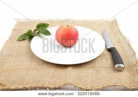 Colorful and crisp image of apple with knife and leaves on jute