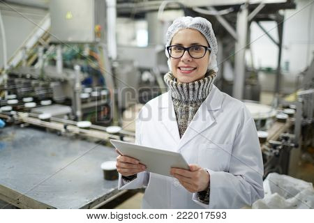 Young staff of seafood plant in uniform browsing in the net at workplace