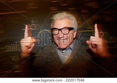 Genius mature teacher keeping his forefingers raised and looking at camera