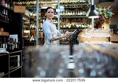 Young staff of restaurant standing by computer and entering data about latest orders and payments
