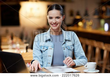 Young female accountant sitting by table in cafe, working with papers, making notes and browsing in the net