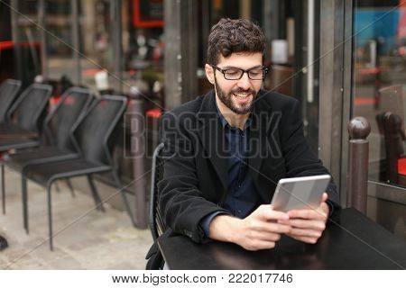 Male graphic designer working with order papers and modern tablet in  . Attractive man has glasses and beard. Concept of creating visual concepts using computer software.