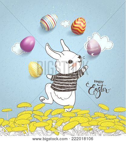 Funny hand drawn baby rabbit wearing striped t-shirt juggling with decorated eggs on floral meadow and Happy Easter handwritten inscription against blue background with clouds. Vector illustration.