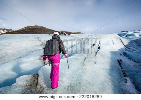 Private Guide And Couple Of Hiker Walking On Glacier At Solheimajokull