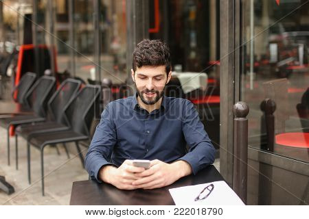 Gladden male person sitting at cafe table and chatting with wife by smartphone with close up face in  .  Young man enjoying rest at break. Concept of sharing feelings using modern gadgets and Internet.