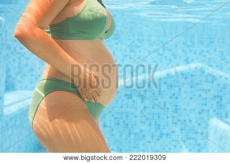 Young pregnant woman in green bikini swimming in pool. Underwater shot