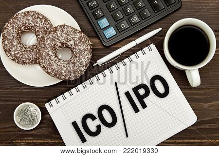 Notebook with a Business notes ICO initial coin offering vs IPO Initial Public Offering on the office table with tools. Concept IPO and ICO
