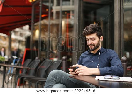 Happy businessman typing message to partner and wondering with successful surprise in  . Handsome male person dressed in classic style blue shirt and grey jeans sitting at street cafe near glasses and papers on table. Concept of pleasant biz achievements