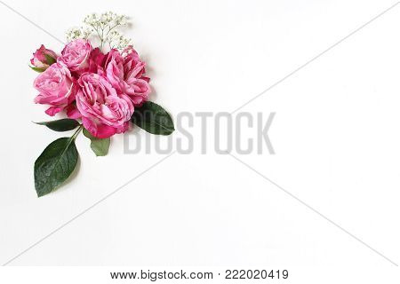 Decorative floral composition with pink roses, green leaves and and baby's breath Gypsophila flowers on white table background. Flat lay, top view, wedding or birthday styled stock photo.