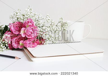 Wedding styled stock photo. Still life with pink roses, baby's breath Gypsophila flowers, white cup, pencil and notebook, floral composition. Image for blog or social media.