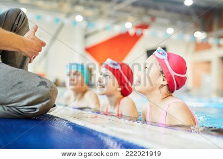 Row of three schoolkids in swimwear looking at their trainer out of water and listening to him