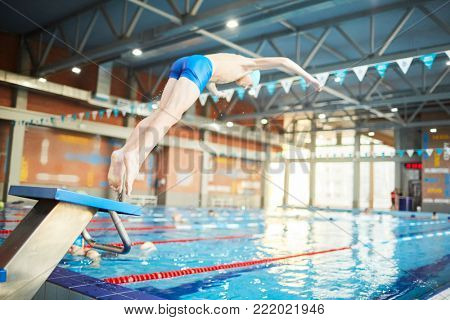 Adolescent boy in swimwear doing jump into water of swimming-pool from diving board