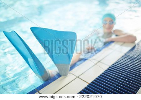 Blue flippers on feet of young swimmer enjoying leisure in swimming-pool