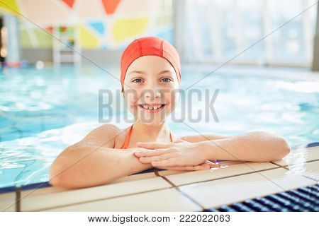 Happy little girl in swimwear looking at camera out of swimming-pool