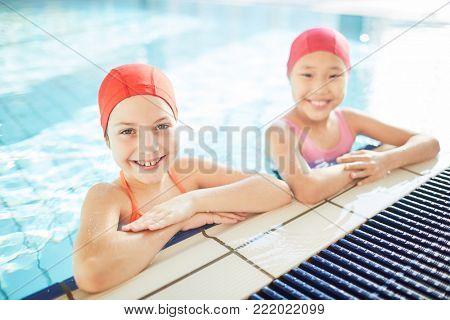 Happy intercultural schoolgirls in swim-caps and swimwear looking at camera in swimming-pool