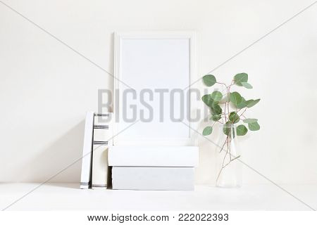 White blank wooden frame mockup with a green eucalyptus branches in glass bottle and pile of books lying on the table. Poster product design, styled stock feminine photography. Home decor.