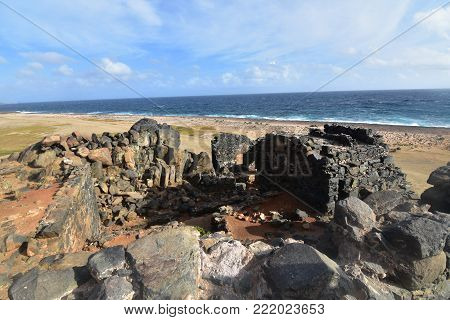 Breathtaking view of the ruins of a gold mill with the ocean in the background