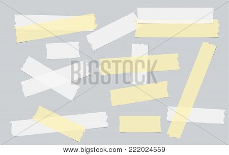 Yellow and white different size adhesive, sticky, masking, duct tape, paper pieces on gray background
