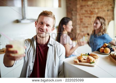 Happy guy cheering up with homemade drink with two girls talking on background