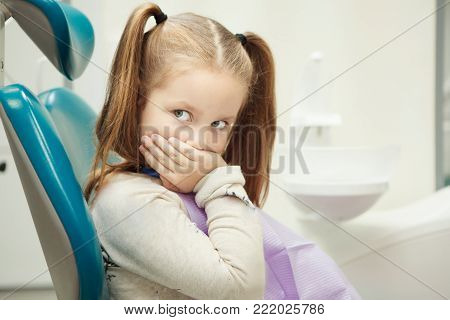 Little child with wide open green eyes and ginger hair sits at dentist office in comfortable leather chair holds her mouth with hand, scared of painful procedure.