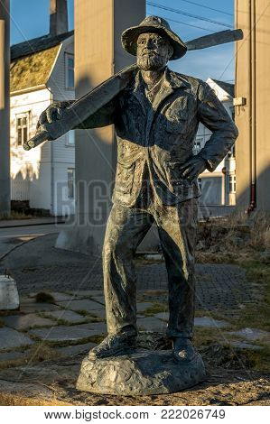 Haugesund, Norway - January 9, 2018: The statue of Ola Flytt, standing at Risoya in Haugesund is made by Arne Meland. Ola Flytt was a well known and beloved ferryman working in Haugesund from 1876 to around 1916.