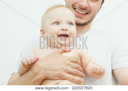 Smiling happy baby in father's hand. Little enfant toddler, lovely son or daughter with blonde hair and blue eyes.