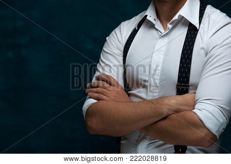 Hands of an unidentified strong man in formal attire with suspenders folded on chest on blue grunge background