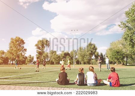 Children Soccer Team Playing Match. Football Game for Kids. Young Soccer Players Sitting on Pitch. Little Kids in Blue and Red Soccer Jersey Sportswear waiting in a out