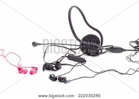 Different red and black earphones, black wireless earphones and headset with full size headphones and microphone closeup on a white background