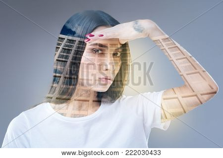 In search. Appealing good looking ambitious woman looking for variants  and gazing at the camera while placing hand near forehead