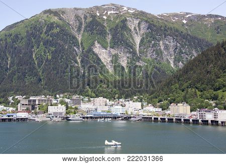 The airplane landed on a water in front of Juneau downtown and Juneau Mountain (Alaska).
