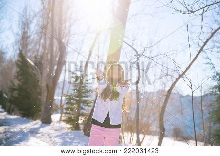 Little girl catching snowflakes in winter park, happy active child, having fun outdoors in bright sunny day, enjoying winter holidays, playing games outdoor