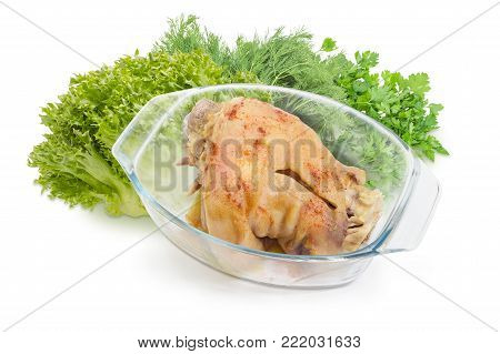 Baked ham hock sprinkled with spices in glass casserole pan on a background of bunches of lettuce, parsley and dill on a white background
