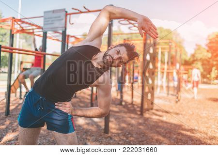 Man doing arms exercise. Industrial workout. Warming before sport. Portrait of strong guy doing muscles exercises on training apparatus outdoors, fit pumps biceps at seashore horizontal bar, sportsman at physical activity