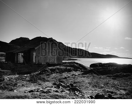 Beautiful view on norwegian bay with traditional  houses along rocky coastline. Outdoor spring shot in Norway.