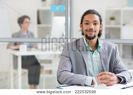 Young well-dressed African-american businessman looking at camera by workplace in office environment